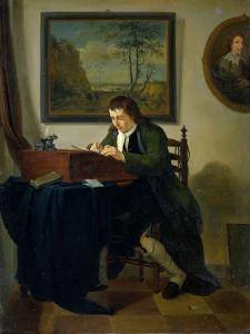 机で書き物をする男