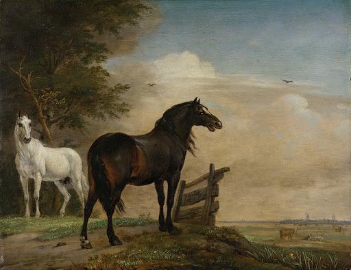 門の近くの牧草地にいる二頭の馬